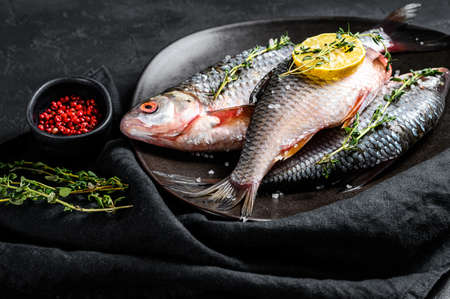 Raw crucian carp with lemon and thyme on a black plate. River organic fish. Black background. Top view.