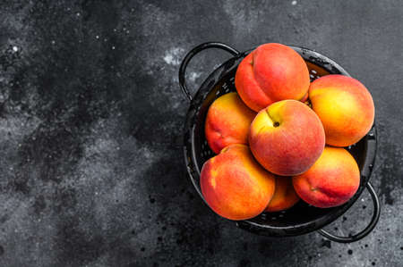 Peaches fruit in a black colander on the table. Black background. Top view. Copy space.