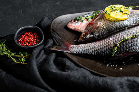 crucian carp with lemon and thyme on a black plate. River organic fish. Black background. Top view.