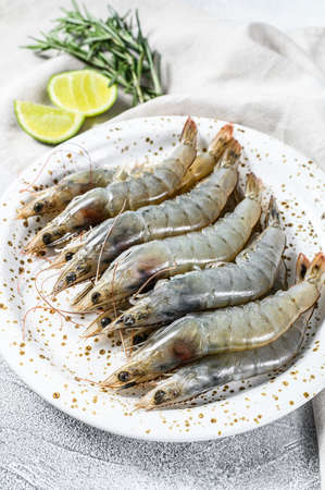 Fresh raw tiger prawns, shrimps and spices on a white plate. Gray background. Top view. Stock Photo