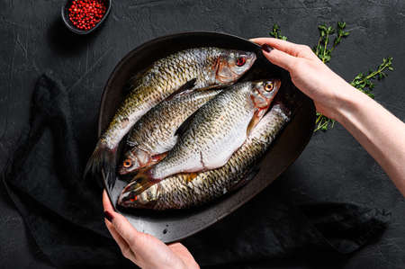 The chef holds a plate of crucian carp. River organic fish. Black background. Top view. Space for text.