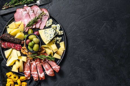 Typical italian antipasto with prosciutto, ham, cheese and olives. Black background. Top view. Space for text.