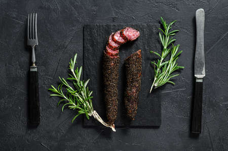 Fuet sausage cut in slices on a black slate plate with rosemary. Black background. Top view. Reklamní fotografie