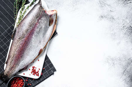 Raw rainbow trout fish with salt and thyme. Gray background. Top view. Copy space.