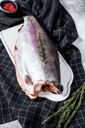 Fresh rainbow trout fish marinated with salt and thyme. Gray background. Top view.