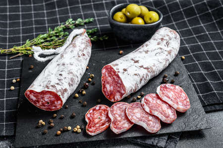Fuet Salami cut in slices and Rosemary. Traditional Spanish sausage. Black background. Top view.