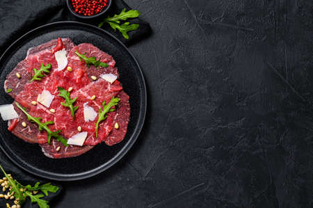 Marbled beef carpaccio with arugula and parmesan cheese. Black background. Top view. Space for text.