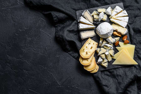 Cheese plate served with nuts and figs. Black background. Top view. Space for text.