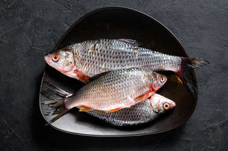 Raw crucian carp on a black plate. River organic fish. Black background. Top view. Reklamní fotografie