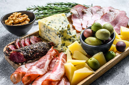 Antipasto platter with ham, prosciutto, salami, blue cheese, mozzarella and olives. Gray background. Top view. Reklamní fotografie