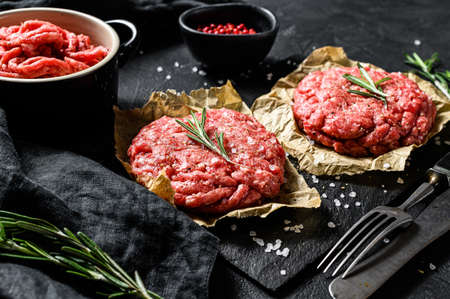 Home HandMade Raw Minced Beef steak burgers. Farm organic meat. Black background. Top view.