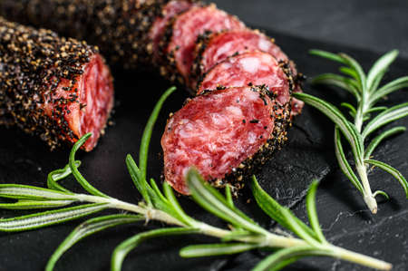 Fuet, Salami and a sprig of rosemary. Traditional Spanish sausage. Black background. Top view. Reklamní fotografie