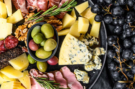 Typical italian antipasto with prosciutto, ham, cheese and olives. Black background. Top view. Reklamní fotografie