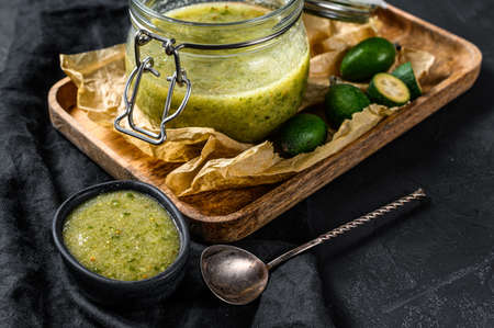 Green feijoa jam on a wooden chopping Board in a glass jar. Natural homemade dessert. Black background. Top view.