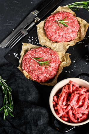 Ground raw meat patties. Meat patties ready to cook. Barbecue party. Farm organic meat. Black background. Top view. 版權商用圖片
