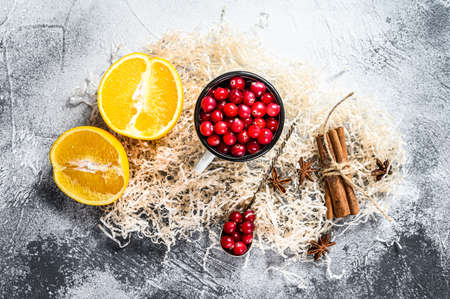 Ingredients for winter baking cookies. Gingerbread, fruitcake, drinks. Cranberries, oranges, cinnamon, spices. Christmas food. Gray background. Top view. 스톡 콘텐츠