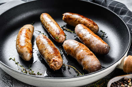 Grilled assorted pork, beef and chicken sausages with spices in a pan. Gray background. Top view.