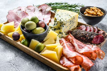Italian appetizers or antipasto set mixed delicatessen of cheese and meat snacks. Gray background. Top view.