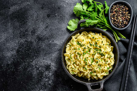 Cooked Instant noodles with soy meat in a pot. Vegetarian dish. Black background. Top view. Copy space. 免版税图像