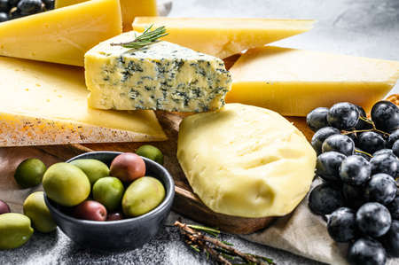 Different pieces of cheese with nuts olives and grapes. Assorted delicious snacks. Gray background. Top view.