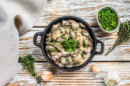 Beef stroganoff with mushrooms in frying pan. White background. Top view.