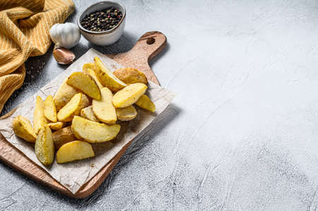 Frozen potato wedges on a cutting board. Recipe for French Fries. White background. Top view. Copy space.