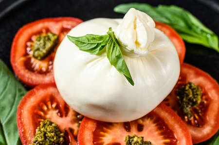 Buffalo burrata cheese served with fresh tomatoes and basil leaves. Black background. Top view.