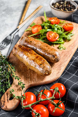 Barbecue grilled pork Sausages with a side dish of tomato salad and arugula. Gray background. Top view. 版權商用圖片