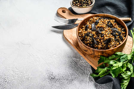 Buckwheat porridge with mushrooms. Vegan food. Russian, Ukranian cuisine. Gray background. Top view. Copy space.