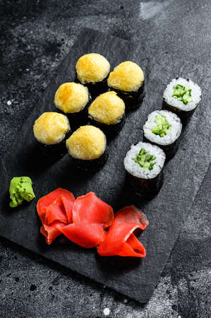 sushi rolls with cucumber, salmon and shrimp on a stone tray. Black background. Top view.