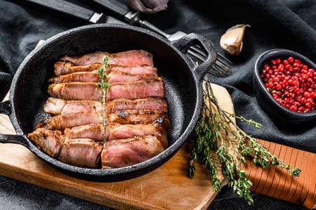 Fried sliced marble pork steak in a pan. Organic meat. Black background. Top view.