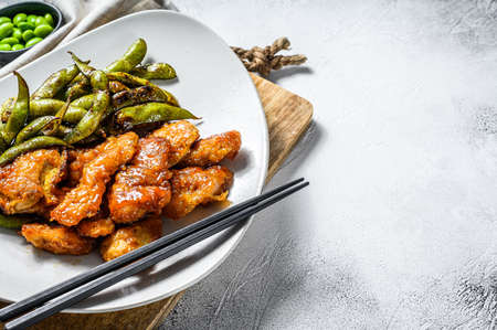 Sweet and sour chicken with beans edamame on a plate. Chinese dish. White background. Top view. Copy space. Archivio Fotografico