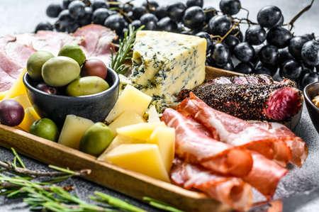 Antipasto platter with ham, prosciutto, salami, blue cheese, mozzarella and olives. Gray background. Top view. 版權商用圖片