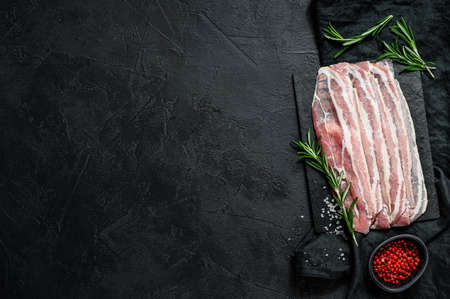 Raw bacon on a stone chopping Board. Pork meat. Black background. Top view. Space for text. 写真素材