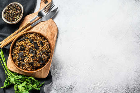Buckwheat porridge with mushrooms in a wooden pot. Gray background. Top view. Copy space.