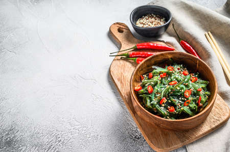 healthy seaweed chuka salad with greens and red chili pepper. Gray background. Top view. Copy space.