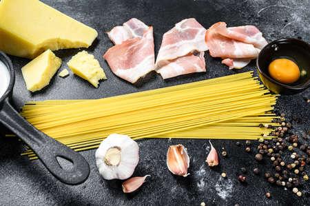 Traidtional Italian Pasta Carbonara Ingredients. Bacon, Spaghetti, Parmesan and pecorino cheese, egg, garlic. Black background. Top view. 版權商用圖片