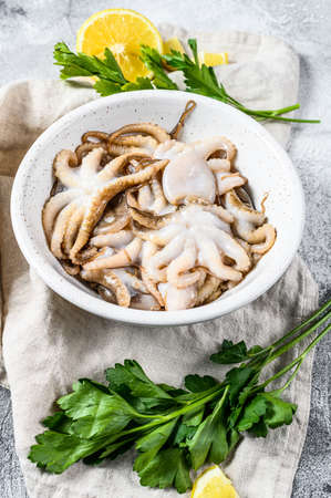 Raw octopus with parsley and lemon in a white bowl. Organic seafood. Gray background. Top view.