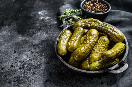 Marinated pickled cucumbers with herbs and spices. Black background. Top view. Copy space.