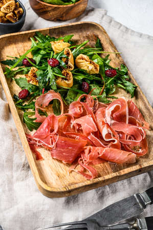 Salad with Serrano jamon, ham, rucola and fig. Antipasto. Gray background, top view
