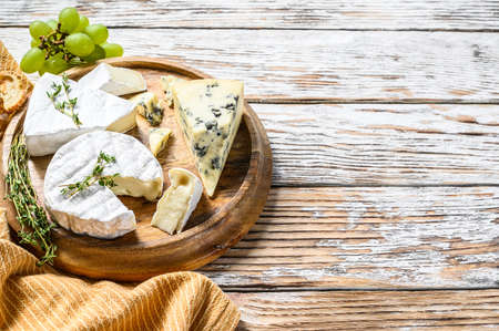 Cheese plate with Camembert, brie and blue cheese with grapes. White wooden background. Top view. Copy space. 写真素材