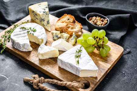 Cheese Board with French Camembert, brie and blue cheese, grapes and walnuts. Black background. Top view.