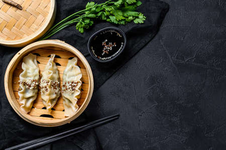 Japanese gyoza in a traditional bamboo steamer. Top view. Space for text. rustic old vintage black background. Zdjęcie Seryjne