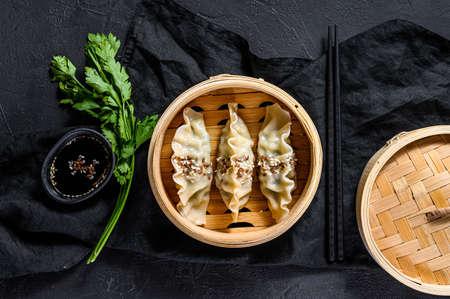 Korean dumplings in a traditional bamboo steamer. Top view. Rustic old vintage black background.