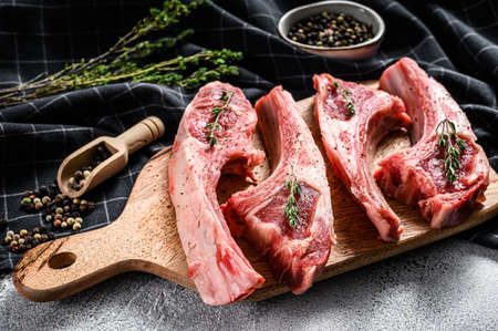 Raw fresh lamb ribs with pepper and thyme. Organic meat. White background. Top view.
