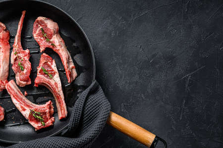 Rack of lamb , raw meat with bone. Organic lamb meat. Black background. Top view. Copy space. Archivio Fotografico