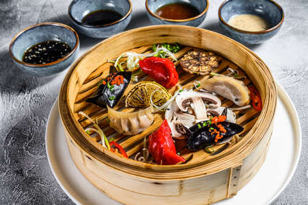 Assorted dim sum appetizers in a bamboo steamer. Set of Chinese food. Gray background. Top view. Zdjęcie Seryjne