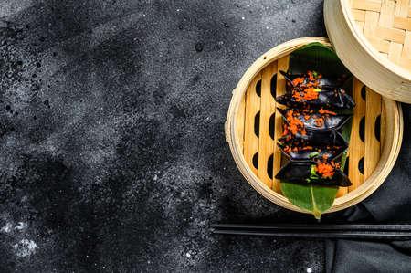 Black Dim sum dumplings in bamboo steamer. Asian cuisine. Black background. Top view. Copy space.