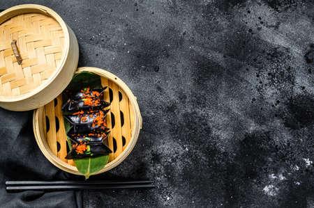 Steamed dumplings Dim Sum in bamboo steamer. Black background. Top view. Copy space.