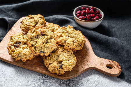 Freshly baked cranberry oatmeal cookies on wooden cutting board. White background. Top view.